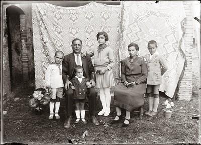 Retrat d'estudi de llençol d'un matrimoni assegut amb els seus fills dempeus