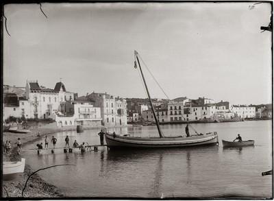 Vista panoràmica de la platja Gran de Cadaqués amb uns homes feinejant prop d'una barca varada, dita Pedro. A la imatge ja es pot veure la casa Serinyana construïda el 1914.