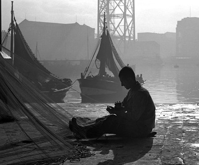 Pescador remendant xarxes en el Moll de Pescadors ( Barcelona )