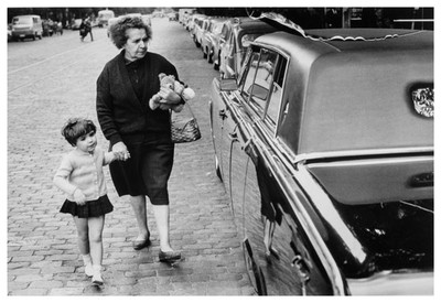 Àvia i néta miren encuriosides un cotxe modern als carrers de Madrid