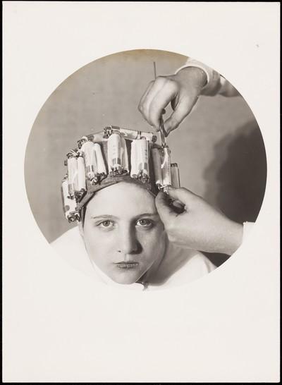 Fotografia publicitària d'una dona fent-se la permanent per un perruquer